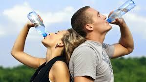 mujer y himbre bebiendo agua mineral