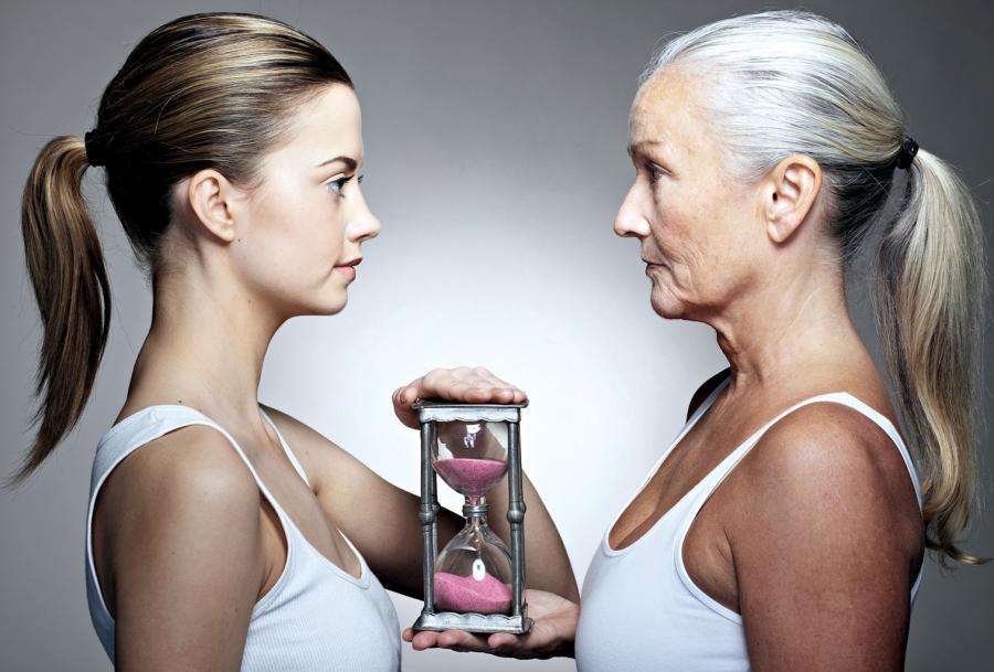 Mujer joven y mas mayor con reloj del tiempo
