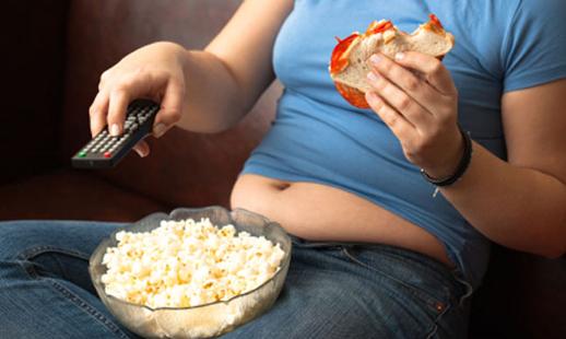 Persona en el sofá comiendo mal