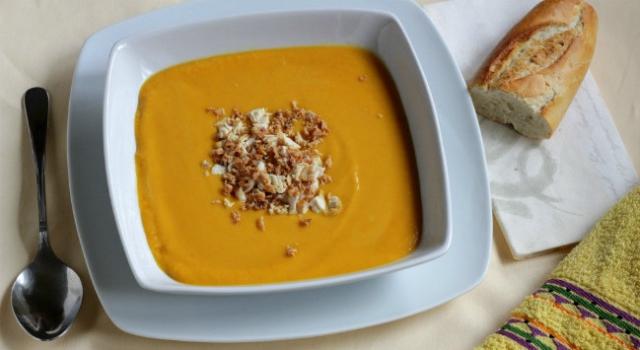 Plato con crema de coliflor patata y zanahoria , cubiertos y pan