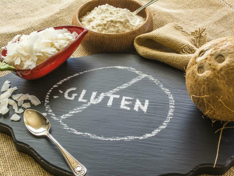 Tabla de pizarra donde aparece la palabra gluten tachada y varios sacos y cestos alrededor con productos que no pueden comer los celiacos