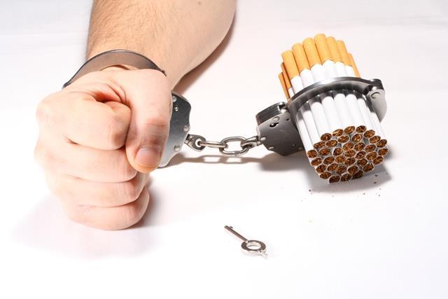 Hombre esposado a un puñado de cigarrillos