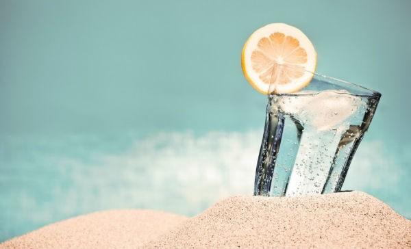 Vaso de cirtsal con agua y limón en arena de la playa con el mar de fondo