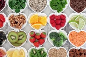 Cuencos en forma de corazón blancos con diferentes alimentos detoxificantes en su interior