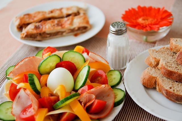 Mesa con platos y diferentes ingredientes de desyauno,bollos,verduras,huevos cocidos,etc...