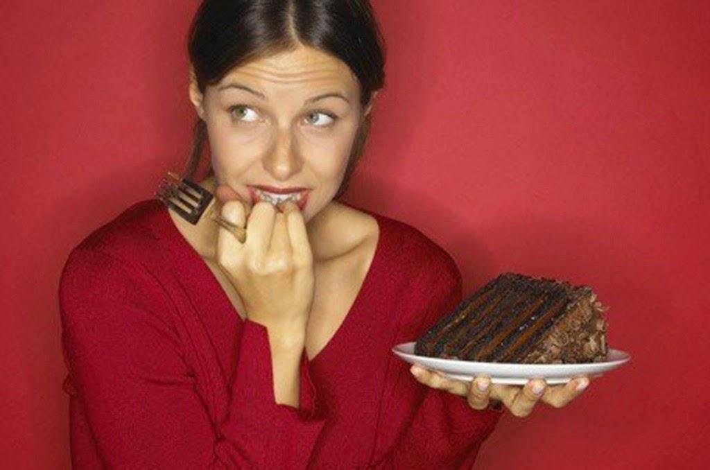 Mujer vestida de rojo con dudas de comerse tarta de chocolate que tiene en la mano en un plato blanco