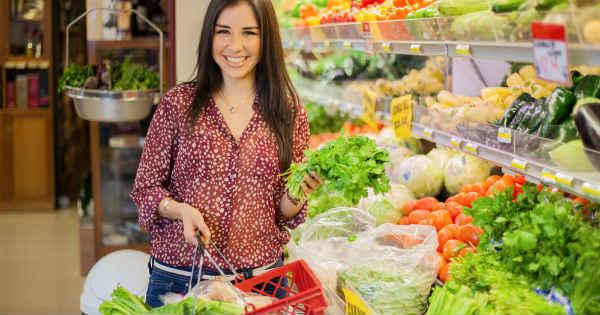 Mujer en el supermercado sonriendo en la zona de verduras con cesta de la compra y lechuga en la mano