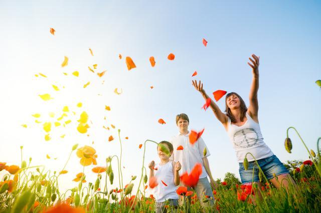 Mujer ocn niños en el campo feliz tirando pétalos de amapolas