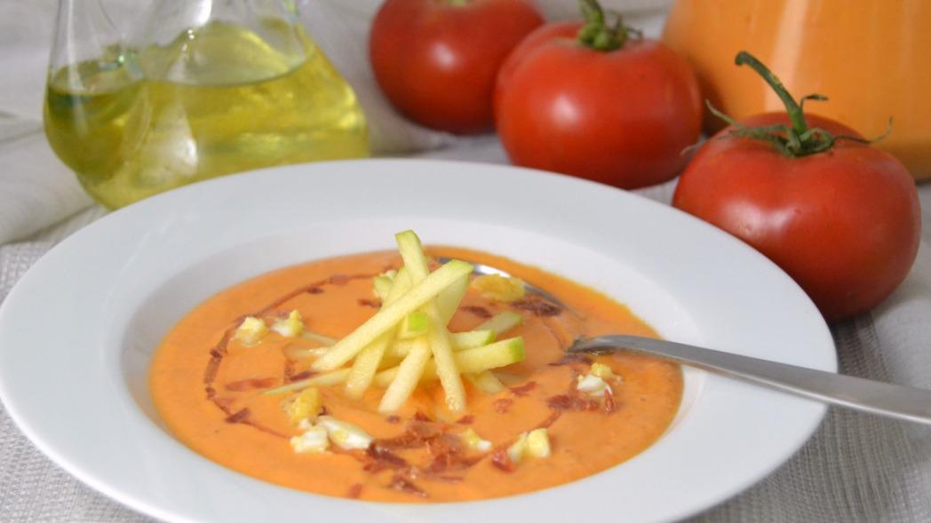 Plato blanco con slamrejo de manzana y de fondo tomates y aceitera