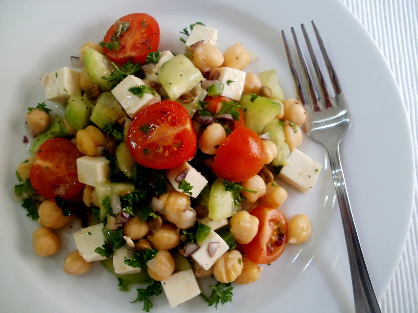 Plato blanco con tenedor de metal con ensalada de garbanzos,tomate y verduras