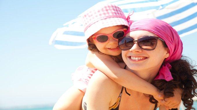 Madre e hija con gafas de sol en la playa