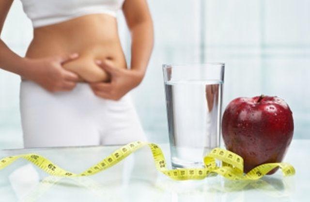 Mujer agarrandose la grasa del abdomen tras una mesa con cintra métrica amarilla,vaso de agua y una manzana