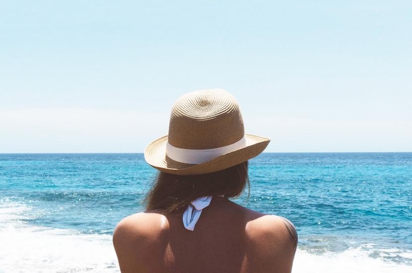 Mujer de espaldas con bikini blanco y sombrero de paja mirando al mar