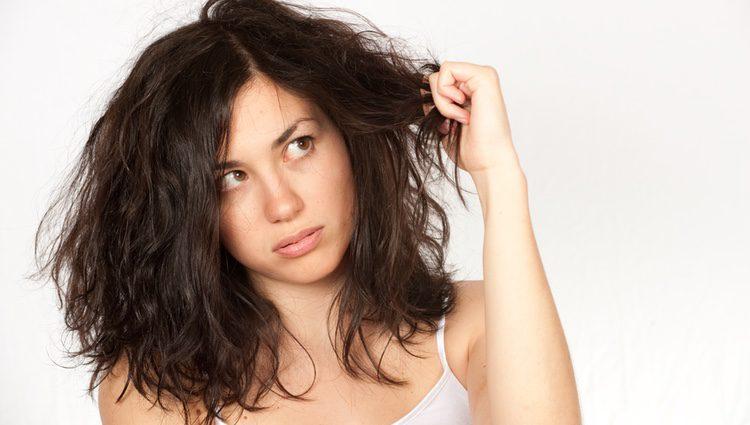 Mujer despeinada mirando su pelo con rabia