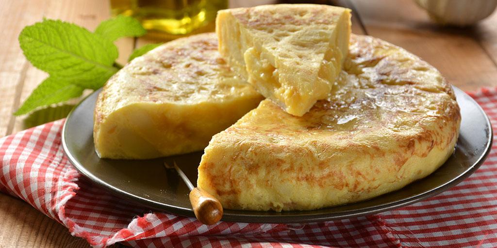 Mantel a cuadros rojo y blanco con plato de tortilla de patatas encima