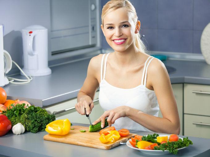 Mujer cortando verduras sonriendo en su cocina