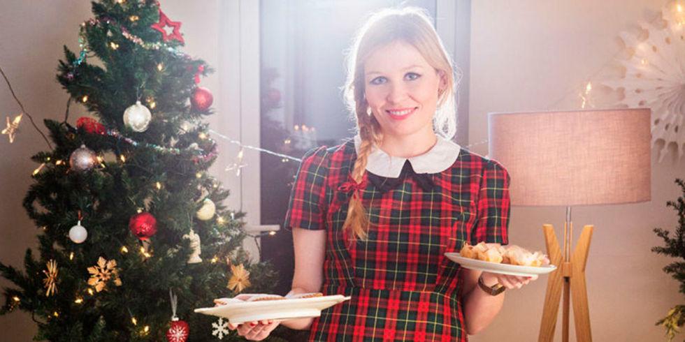 Mujer con vestido de cuadros sujetando platos delante de un árbol de navidad