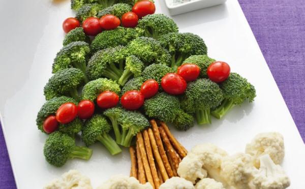 Plato blanco con brocoli, tomates y coliflor simulando un arbol de navidad con sus bolas y la nieve a los pies
