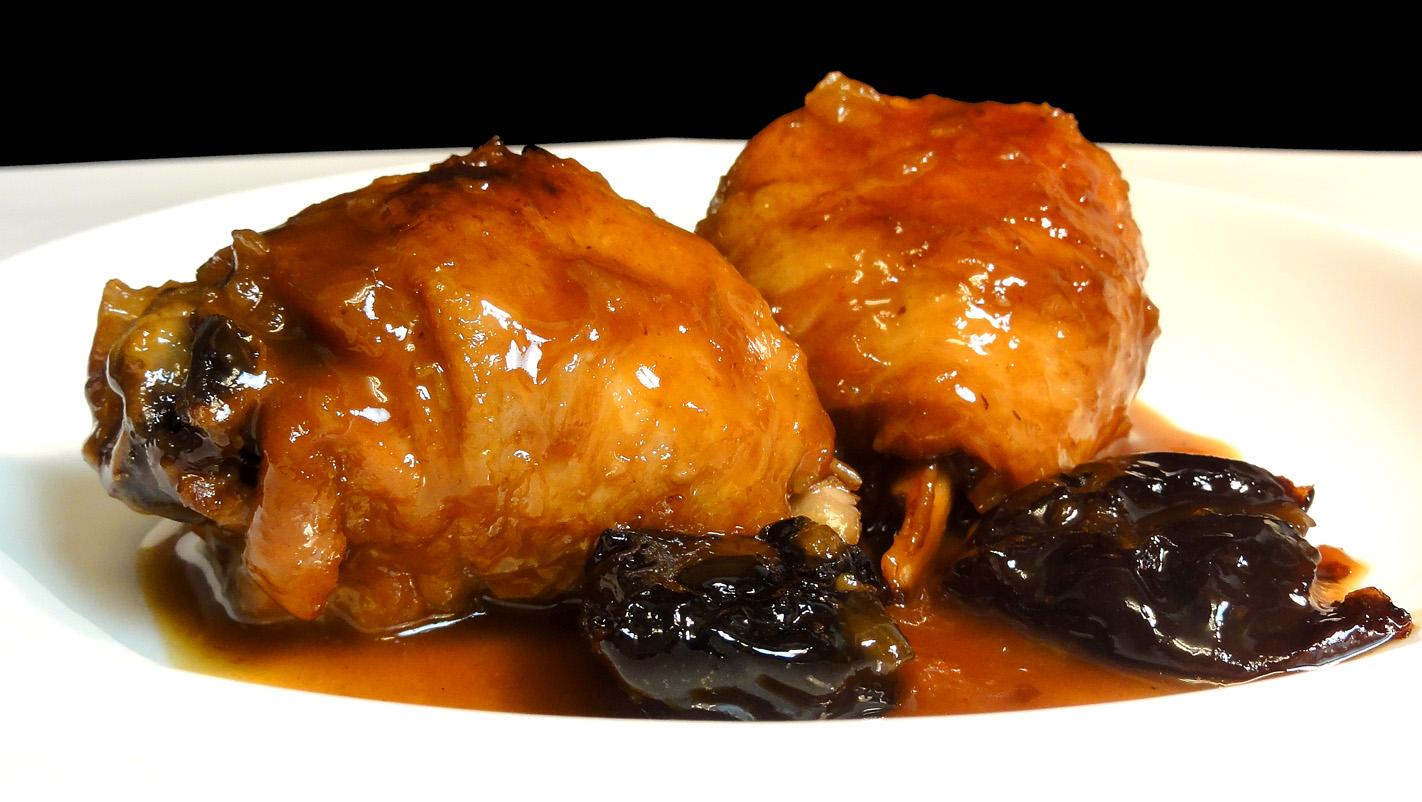Muslos de pollo con salsa de vino dulce y pasas en un plato blanco