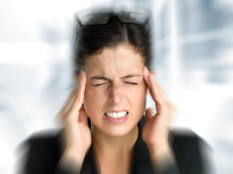 Mujer borrosa tocándose la cabeza como si le doliera