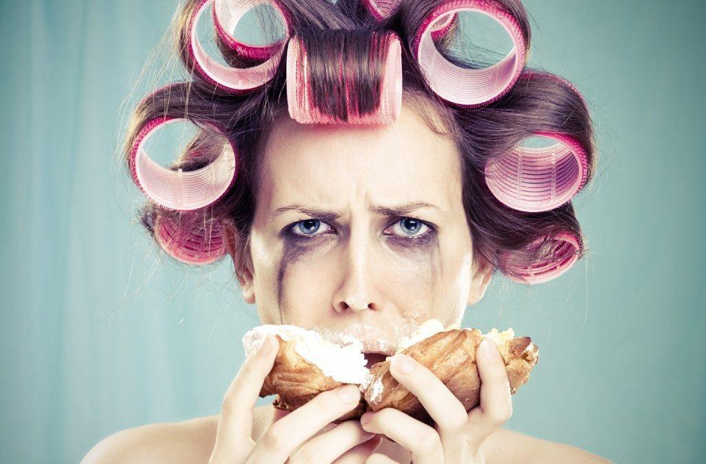 Mujer con rulos en la cabeza llorando y comiendo bollos