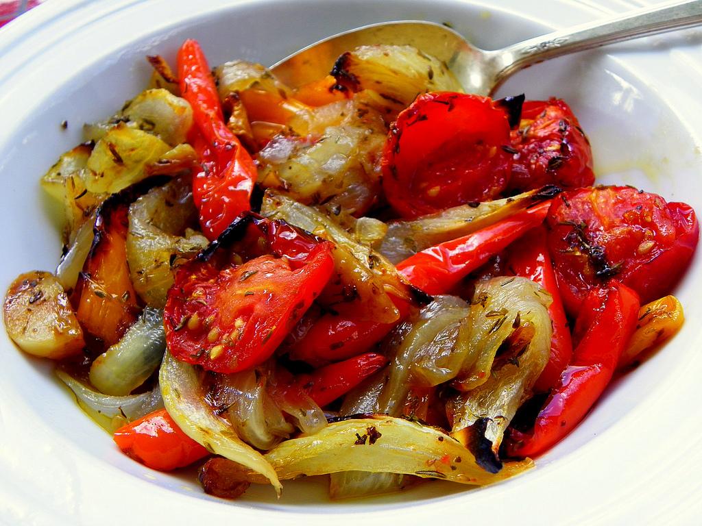 Plato blanco con escalibada de verduras y una cuchara metálica