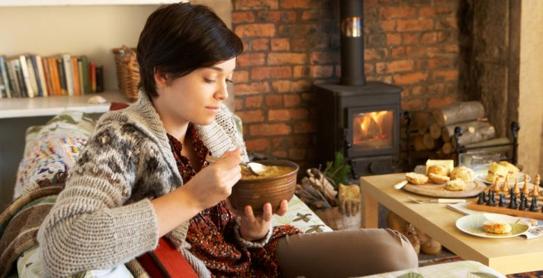 Mujer en invierno con chimenea de fondo comiendo un pure