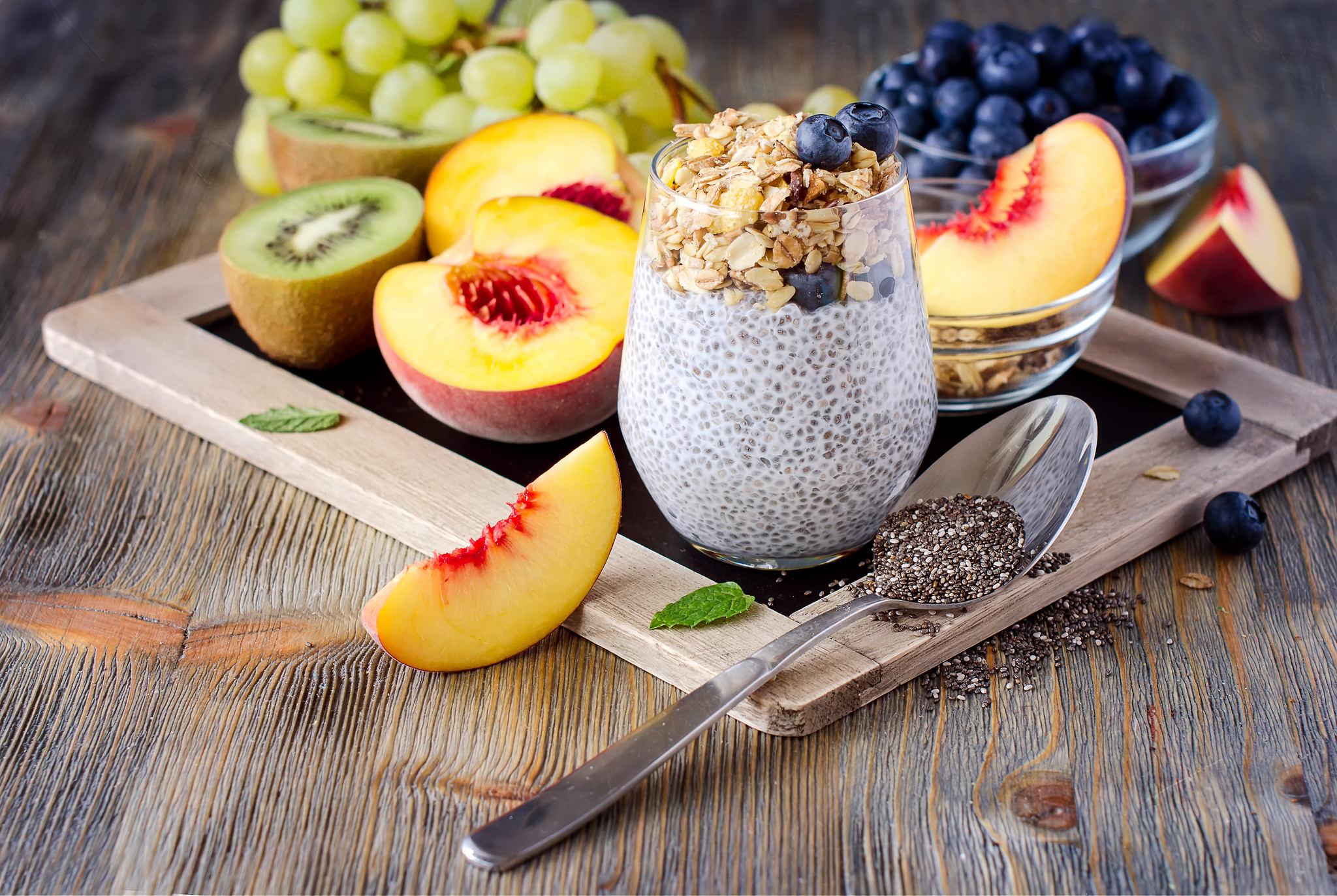 Mesa de madera con fruta,semillas de chia, cuchara metálica...