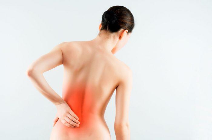 ;ujer desnuda de espaldas tocandose la parte baja de la espalda en la que hay dolor