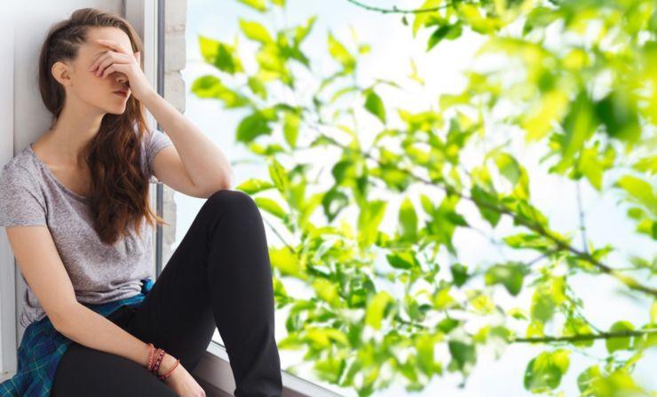 Mujer con mano en cabeza tras una ventana en la que se ve un arbol