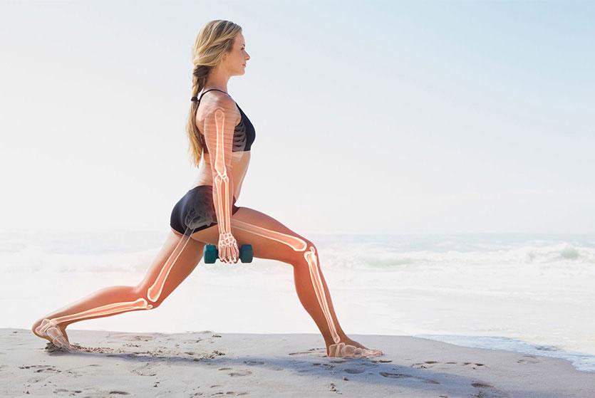 Mujer en la playa con pesas y se leven los huesos y los músculos dibujados