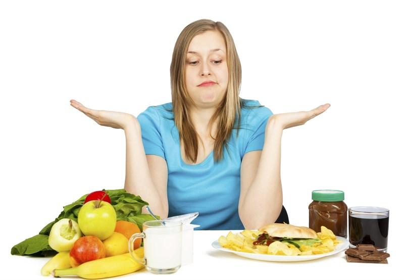 Mujer con diferentes alimentos y dudas sobre que comer