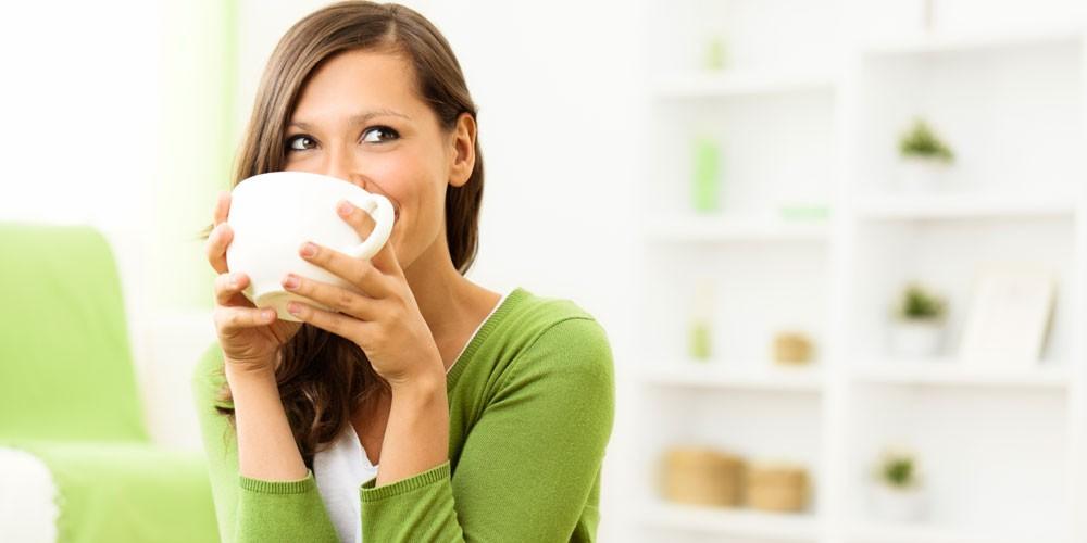 Chica con chaqieta verde bebiendo te en una taza blanca