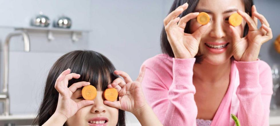 Madre e hija con rodajas de zanahoria en los ojos