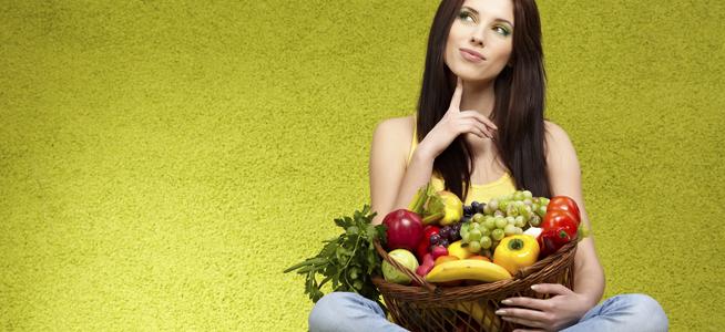 Mujer pensativa con cesta de frutas en la mano sobre fondo verde