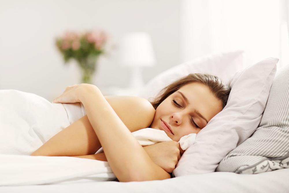 Mujer en la cama durmiendo con una sonrisa