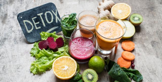 Pizarra donde se lee detoz y alimentos detoxificantes alrededor enteros o en zumo