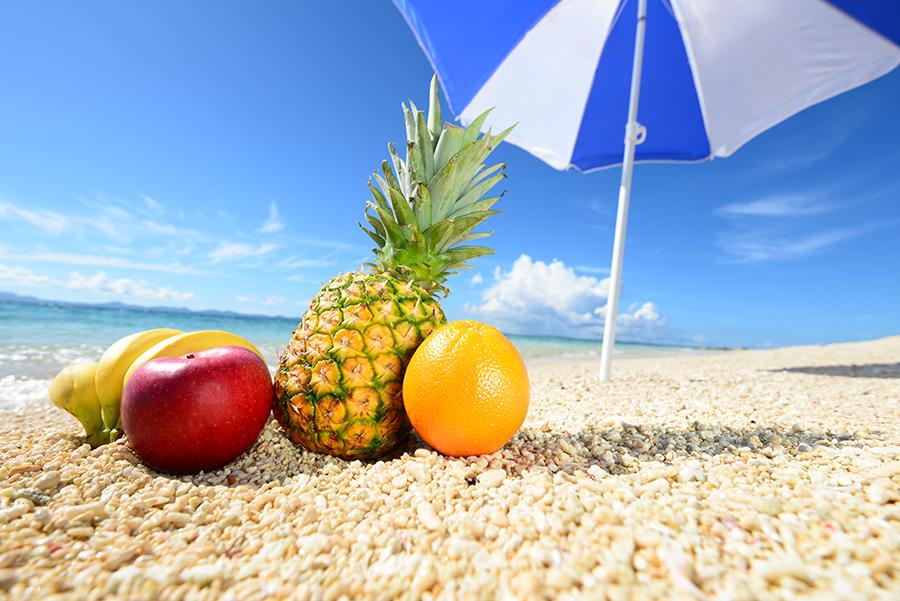 Sombrilla azul y blanca en la playa con frutas como naranja y piña en la arena