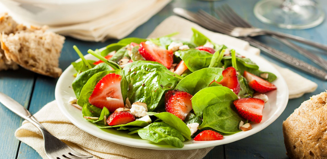 Plato blanco con ensalada de espinacas y fresas