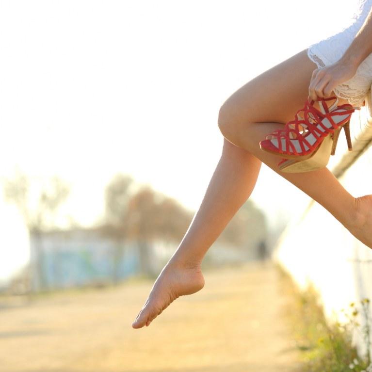Mujer en la playa con piernas colgando en el borde del paseo maritimo