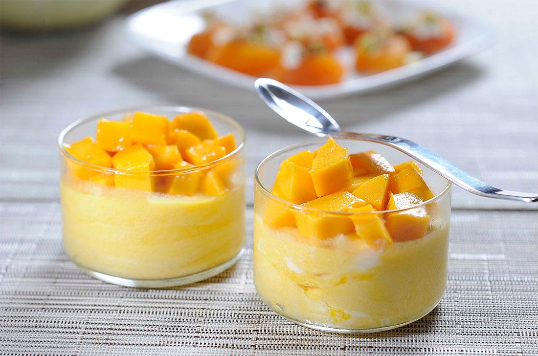 Vasos de cristal con mousse de mango decorada con trozos de mango
