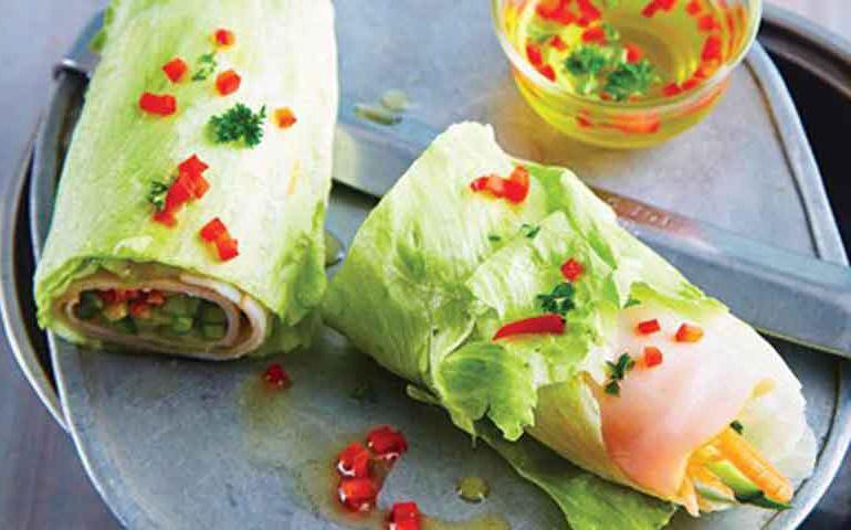 wrap de lechuga con pechuga de pavo y vinagreta de verduras sobre tabla de pizarra