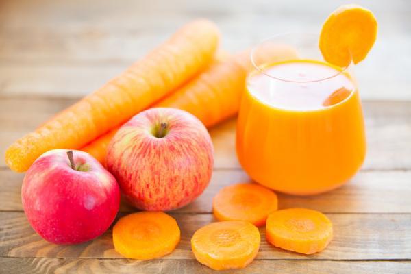 Mesa de madera y encima vaso de cristal con jugo de zanahoria y manza e ingredientes similares obre la mesa