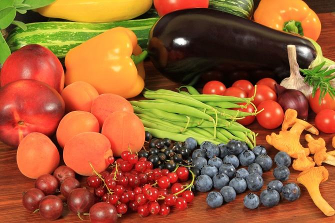 Mesa de madera sobre la que aparecen un montón de frutas y verduras de diferentes colores