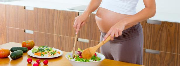 Mujer embaraza en la cocina preparando comida