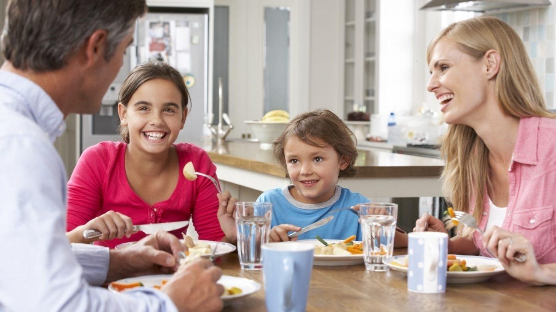 Familia de padre,madre y dos hijas comiendo en mesa de madera y sonriendo