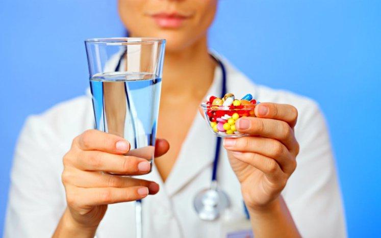Farmaceutica con vaso de agua y en la otra mano vaso con medicamentos