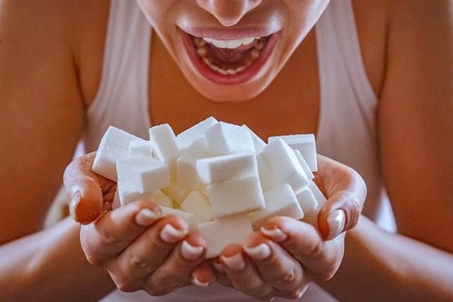 Mujer abriendo la boca queriendo comer un montón de terrones de azucar que sujeta con las manos