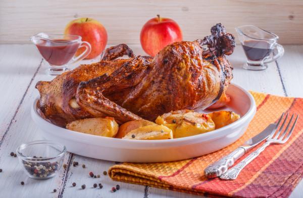 Plato blanco con pato asado con patatas y manzanas decorando alrededor