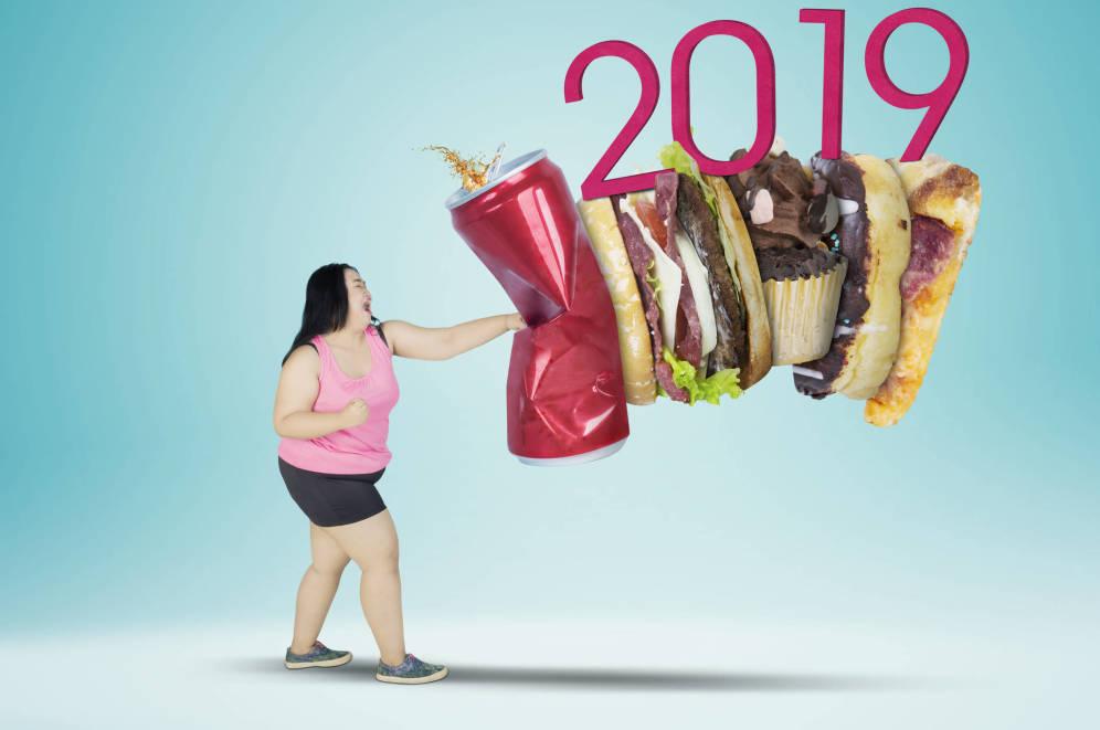 Mujer dando un golpe a la comida basura y de fondo se lee 2019
